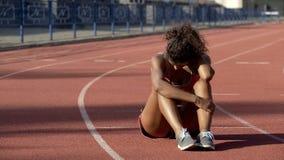 Sportiva biraziale esaurita dopo gli addestramenti duri che si siedono nel mezzo della pista fotografia stock libera da diritti