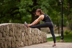 Sportiva che allunga le gambe sul recinto Immagine Stock