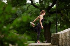 Sportiva che allunga nel parco di estate Immagine Stock Libera da Diritti