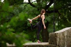 Sportiva che allunga nel parco di estate Fotografia Stock Libera da Diritti