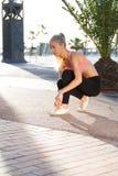 Sportiva che fa esercizio di forma fisica fuori nel parco della palma Immagini Stock Libere da Diritti