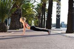 Sportiva che fa esercizio di forma fisica fuori nel parco della palma Immagine Stock Libera da Diritti