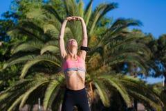 Sportiva che fa esercizio di forma fisica fuori nel parco della palma Immagini Stock