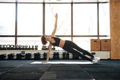Sportiva che fa gli esercizi sulla stuoia in palestra Fotografia Stock