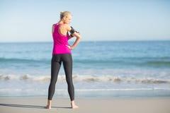 Sportiva che per mezzo del telefono cellulare sulla spiaggia immagini stock libere da diritti