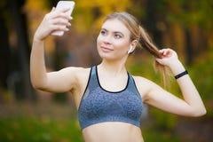 Sportiva che prende una rottura dopo l'allenamento e che per mezzo del telefono all'aperto fotografia stock