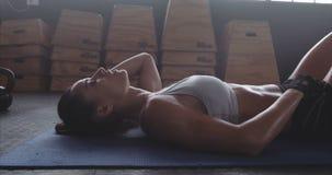 Sportiva che riposa dopo l'addestramento intenso di forma fisica video d archivio