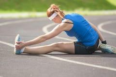Sportiva femminile caucasica che ha muscoli delle gambe che allungano gli esercizi Fotografia Stock Libera da Diritti