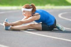 Sportiva femminile caucasica che ha muscoli delle gambe che allungano gli esercizi Immagine Stock
