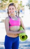 Sportiva sorridente con la stuoia relativa alla ginnastica Immagini Stock