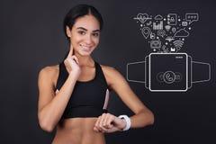 Sportiva sveglia che misura il suoi impulso e sorridere immagine stock
