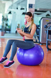 Sportive à l'aide d'un téléphone portable dans le gymnase Image libre de droits