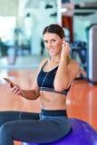 Sportive à l'aide d'un téléphone portable dans le gymnase Photo stock