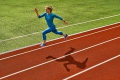 Sportive белокурая тренировка женщины на открытом стадионе стоковая фотография