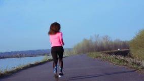 Sportive девушка jogging вдоль речного берега во время восхода солнца или захода солнца здоровая концепция образа жизни атлетичес акции видеоматериалы