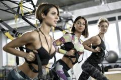 Sportive девушки тренируя в спортзале Стоковая Фотография