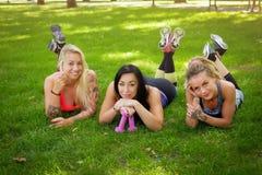3 sportive женских друз лежат на траве на парке outdoors, ослабляющ после разминки, смотря камеру стоковые фотографии rf