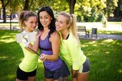 3 sportive женских друз на парке outdoors делают selfie на телефоне с ручкой, усмехаясь стоковые фото