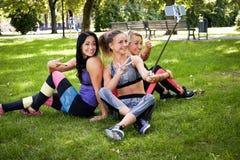 3 sportive женских друз сидя на траве на парке outdoors, делают selfie на телефоне с ручкой стоковая фотография