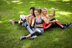 3 sportive женских друз сидя на траве на парке outdoors, делают selfie на телефоне с ручкой стоковые изображения