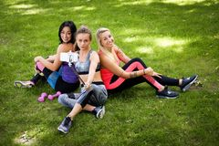 3 sportive женских друз сидя на траве на парке outdoors, делают selfie на телефоне с ручкой стоковые фото