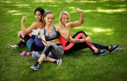 3 sportive женских друз сидя на траве на парке outdoors, делают selfie на телефоне с ручкой стоковые изображения rf