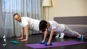 Sportive отец уча его делать сына нажим-поднимает, военная подготовка, выносливость стоковые фотографии rf