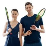 Sportive пары представляя с ракетками стоковое фото