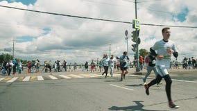 Sportive спортсмены бежать марафон вокруг металла ограждая на перекрестке города сток-видео