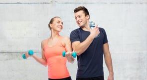Sportive человек и женщина с гантелью и водой стоковые фотографии rf