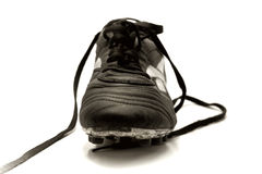 Sportive. Front view of a soccer shoe with dramatic lighting, studio style. Sepia-toned to create mood Stock Images