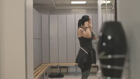 Sportive adult Caucasian woman greeting friend in gym locker room. Side view of positive beautiful sportswomen giving