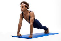 Sportive african man training on karemat over white background. Royalty Free Stock Photos