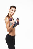 Sportive beautiful girl with dumbbells smiling posing looking at camera over white background. Stock Photo