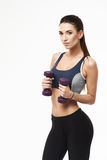 Sportive beautiful girl with dumbbells in sportswear posing looking at camera over white background. Copy space Royalty Free Stock Photo