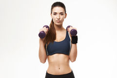 Sportive beautiful girl with dumbbells in sportswear posing looking at camera over white background. Copy space Royalty Free Stock Images