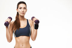 Sportive beautiful girl with dumbbells in sportswear posing looking at camera over white background. Copy space Royalty Free Stock Photography