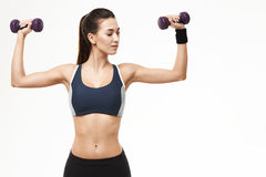 Sportive beautiful girl in sportswear training arms with dumbbells over white background. Copy space Royalty Free Stock Photos