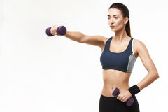 Sportive beautiful girl in sportswear training arms with dumbbells over white background. Royalty Free Stock Image