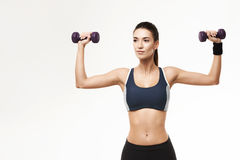 Sportive beautiful girl in sportswear training arms with dumbbells over white background. Copy space Stock Images