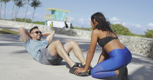 Girl helping man with abs exercise stock footage