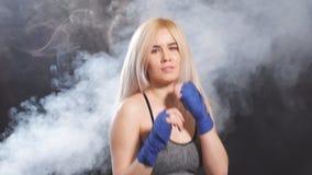 Sportive blonde attirante dans des bandages kickboxing dans la position défensive Mouvement lent banque de vidéos