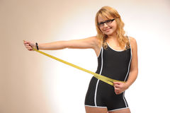 Sportive blonde girl with measuring tape Royalty Free Stock Images