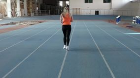 Sportive blonde woman running at indoor stadium. Incredible blonde girl in an orange T-shirt with dark pants and light sneakers is running on the track at the stock video footage