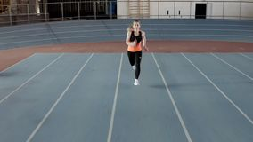 Sportive blonde woman running at indoor stadium. Kyiv, Ukraine - 04 April 2019: blonde girl in a black-orange T-shirt with dark pants and light sneakers is stock video footage