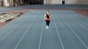 Sportive blonde woman running at indoor stadium. Kyiv, Ukraine - 04 April 2019: blonde girl in a black-orange T-shirt with dark pants and light sneakers is stock video