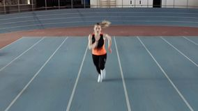 Sportive blonde woman running at indoor stadium. Kyiv, Ukraine - 04 April 2019: blonde girl in a black-orange T-shirt with dark pants and light sneakers is stock footage