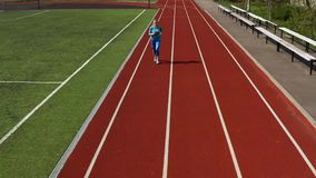 Sportive blonde woman running at open stadium. Kyiv, Ukraine - 04 April 2019: blonde girl in a blue sportswear and sneakers is running on the track at the stock video