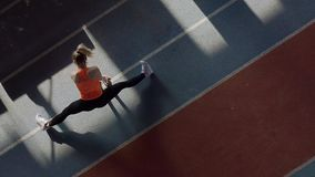 Sportive blonde woman training at indoor stadium. Cute girl in an orange T-shirt with black pants and light sneakers is doing a stretching exercises at the stock video