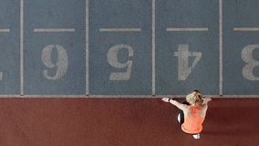 Sportive blonde woman training at indoor stadium. Wonderful blonde girl in an orange T-shirt with dark pants and light sneakers is starting her sprint run on the stock footage